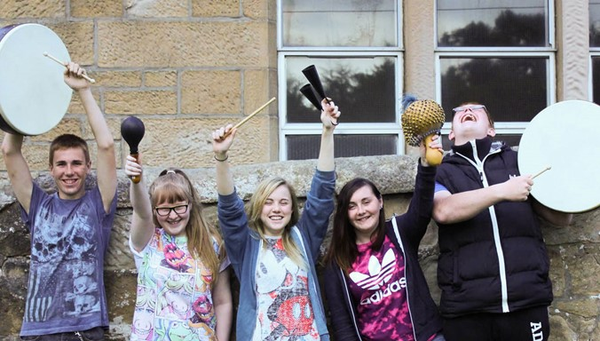 Five young people from Reeltime Music youth club laugh and pose with their musical instruments outside of a sandstone building.