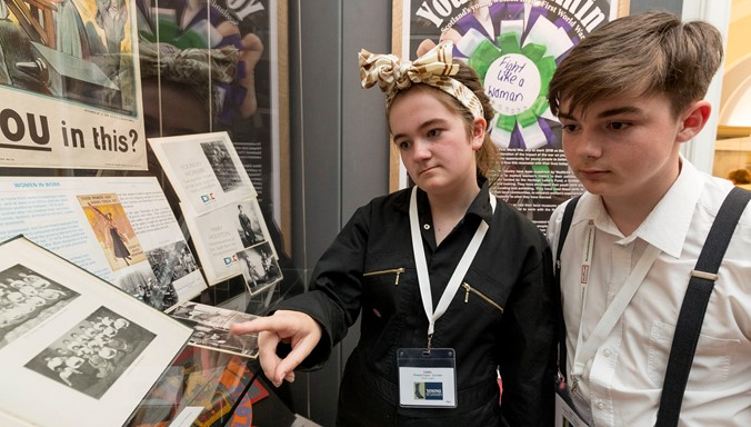 A photograph of a young woman and young man in  WW1 costume looking at an exhibition at the National Library of Scotland.