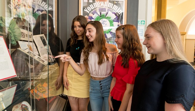 A photograph of four young women looking at an exhibition at the National Library of Scotland.