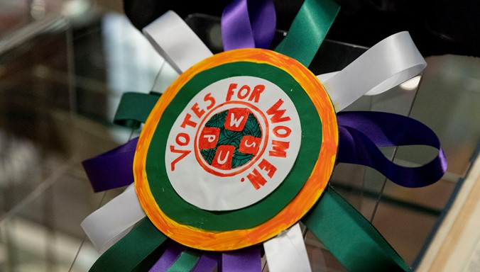 A photograph of a  green and purple rosette made by a young person that reads 'votes for women'.