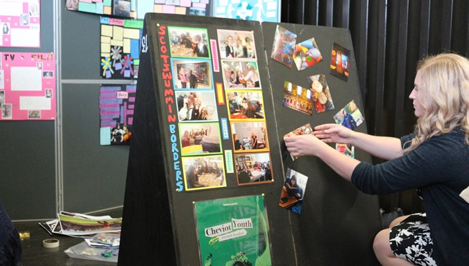 A photograph of a youth worker preparing an exhibition board with content.